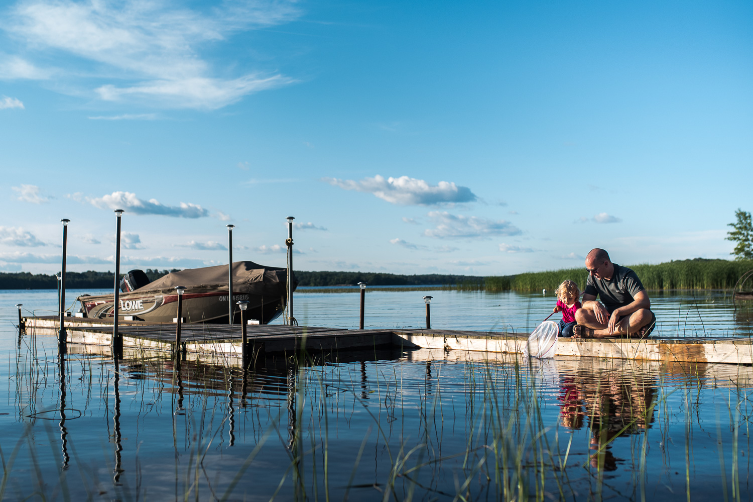 Toddler girl and her dad sitting on a wooden dock in a lake with a boat and a fishing net trying to catch treasures in the lake. Blue Sky and fluffy white clouds reflected in the blue lake water.