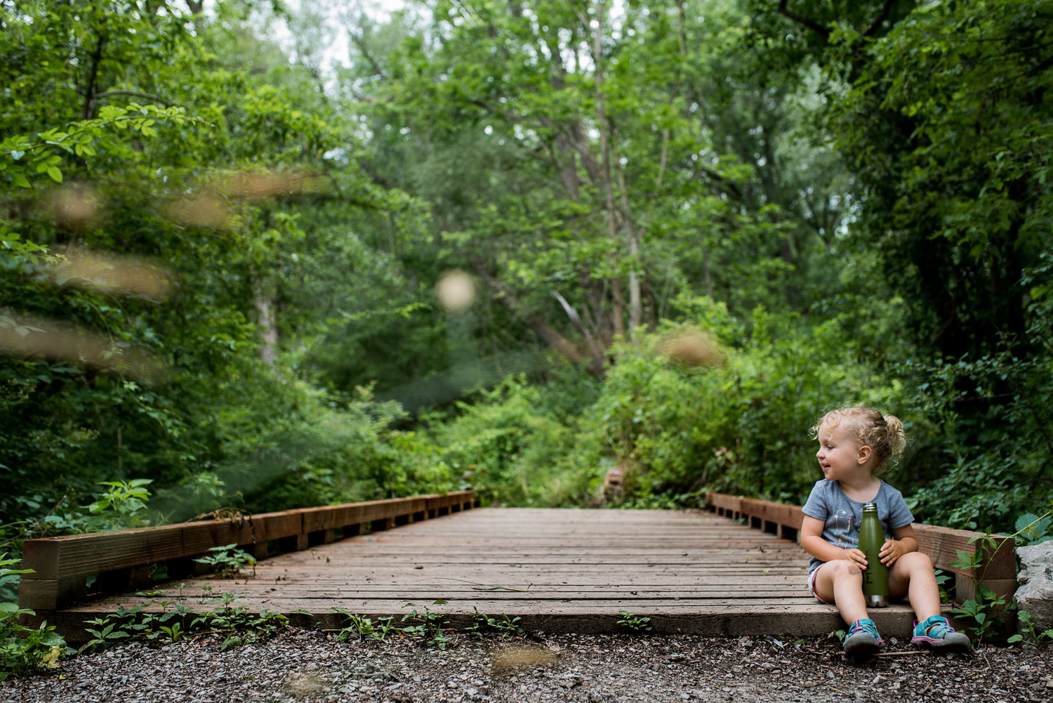 Toddler girl in a grey shirt and light blue sandals sitting on a wooden bridge surrounded by green trees and a grey gravel trail.