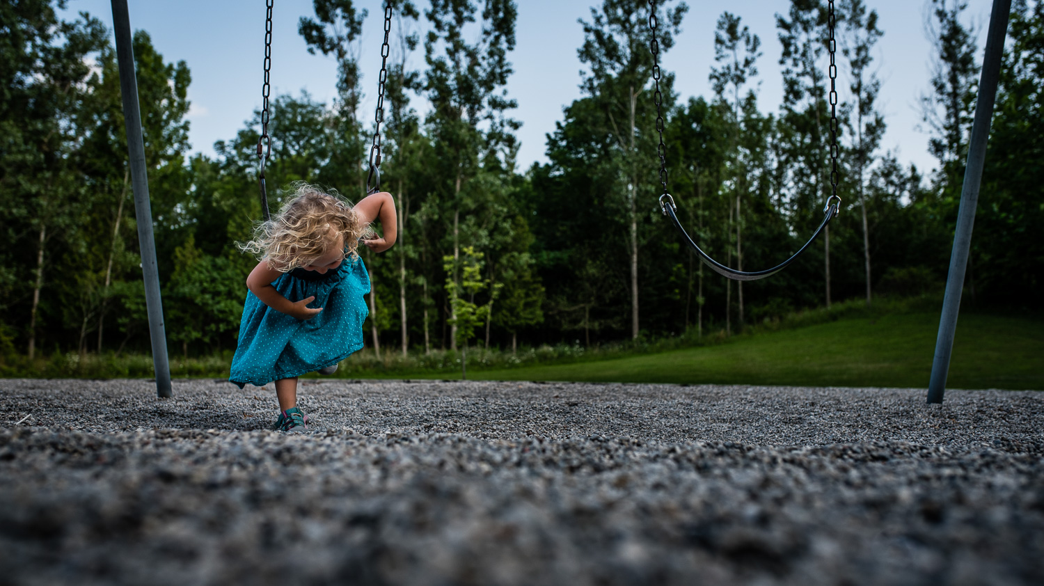Toddler girl with curly hair in a teal blue dress laying on her tummy on a big kid swing over grey gravel with green trees and a blue sky in the background