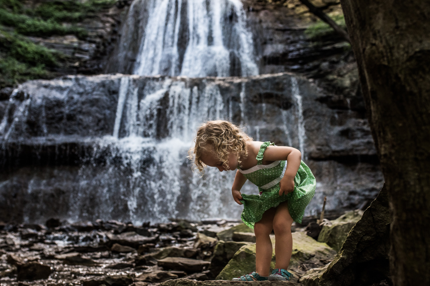Toddler girl with blond curly hair in a green and white polka-dot dress holding up her skirt while standing on a rock with at Sherman Falls trail in Ancaster with a waterfall in the background