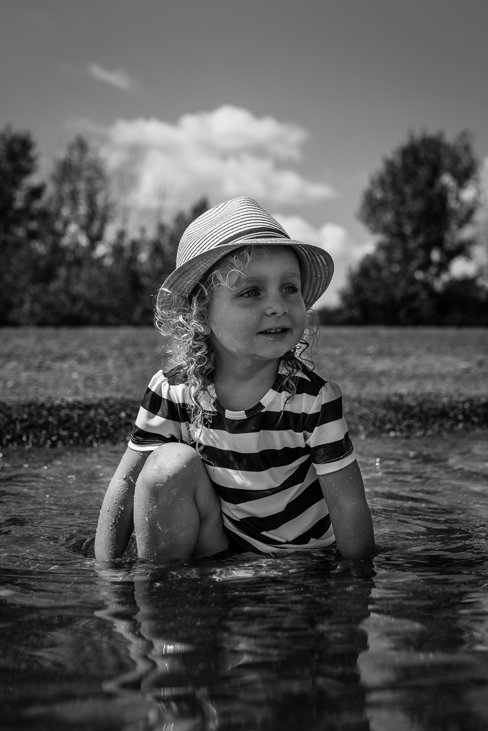 Black and white photograph of a toddler girl in a fedora hat and a stripped UV bathing suit sitting in the beach water with trees and sky with fluffy white clouds behind her.