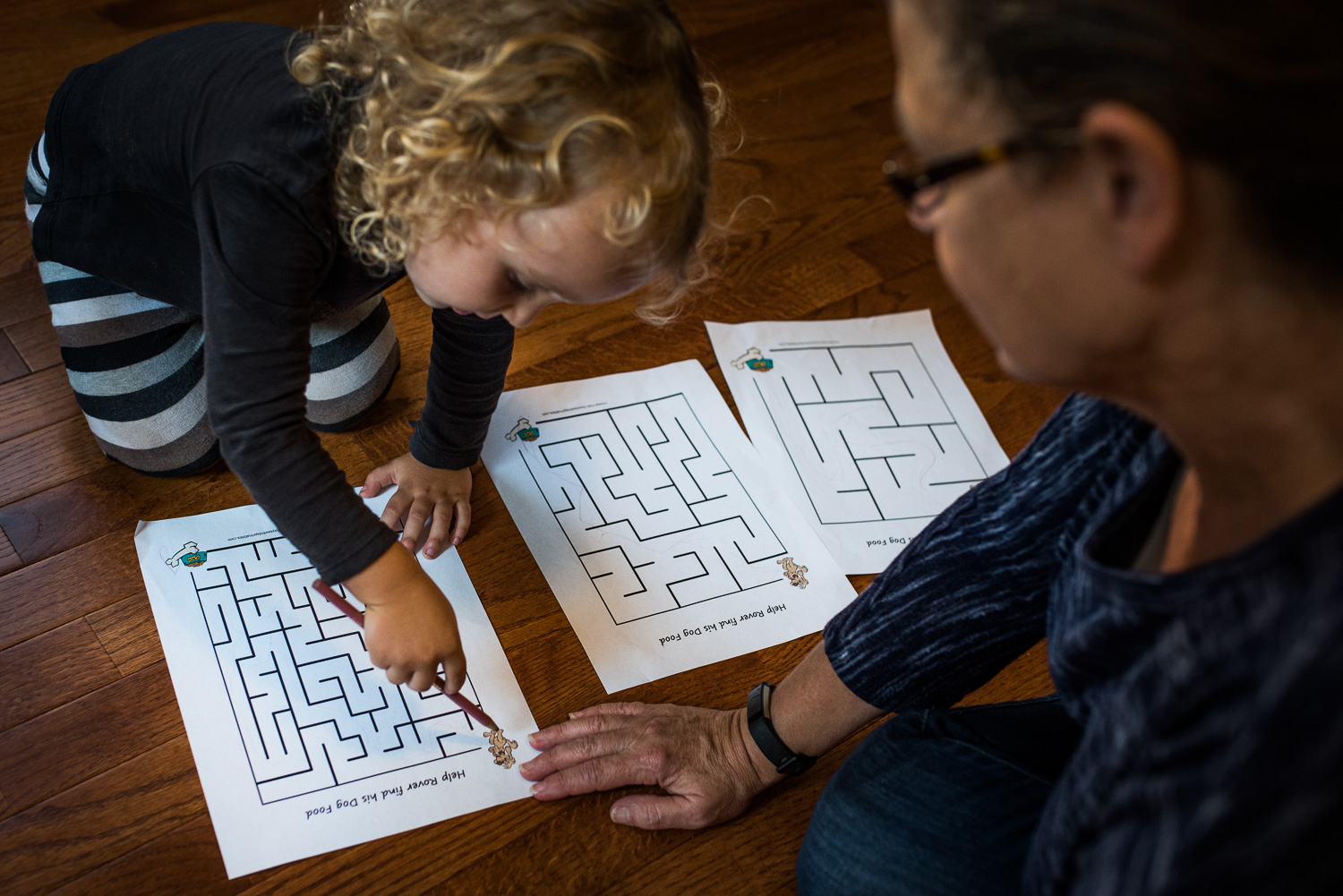 Toddler girl with curly hair sitting on the floor with her grandma working on mazes printed out on white paper