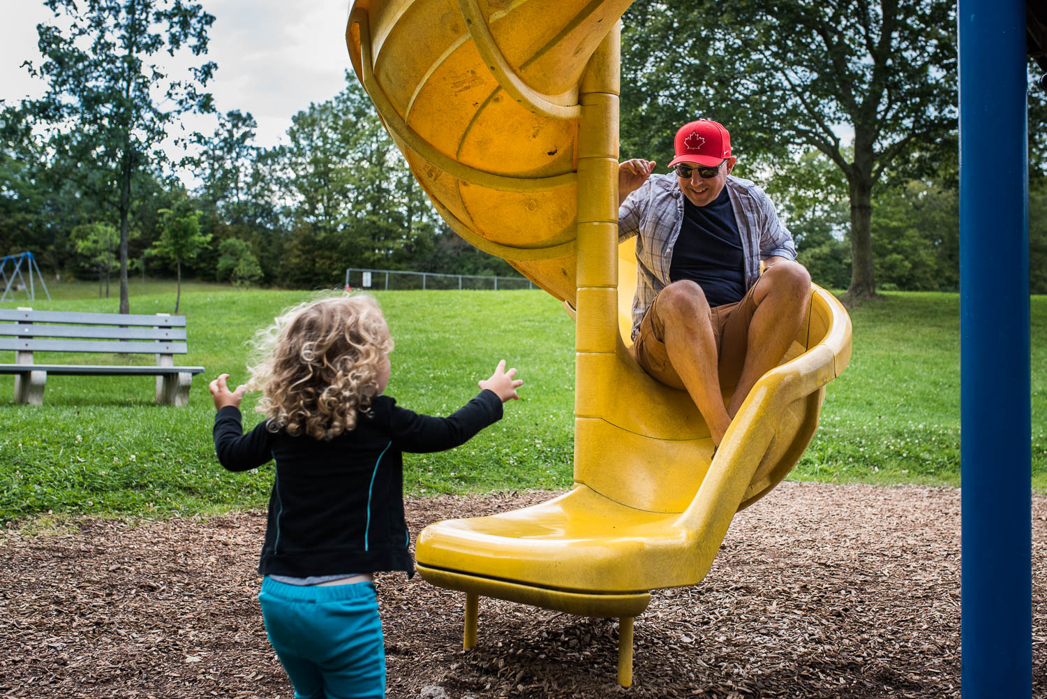 A toddler girl with curly hair at a park running to the bottom of a slide to catch her dad in a red hat who is sliding down the slide