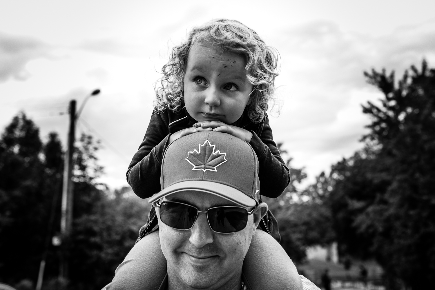 A black and white image of a toddler girl with curly hair sitting on her dad's shoulders resting her hands and head on his head and hat with a canadian maple leaf on it.