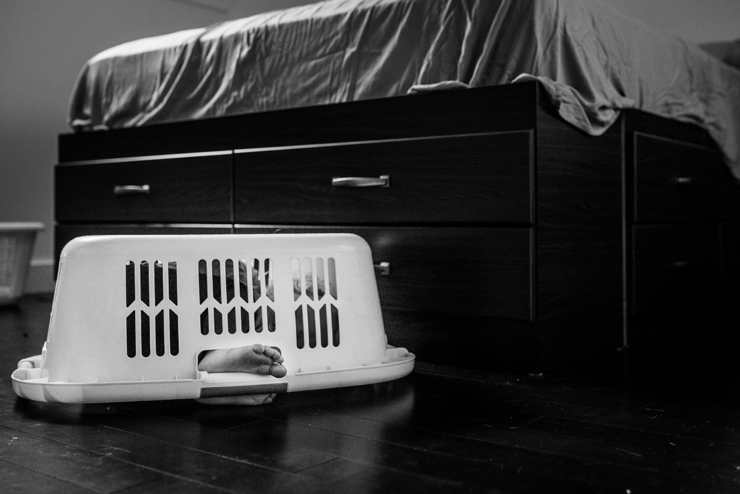Black and white photo of a dark bed with a white laundry basket on the floor with two small toddler feed sticking out of the handle hole.