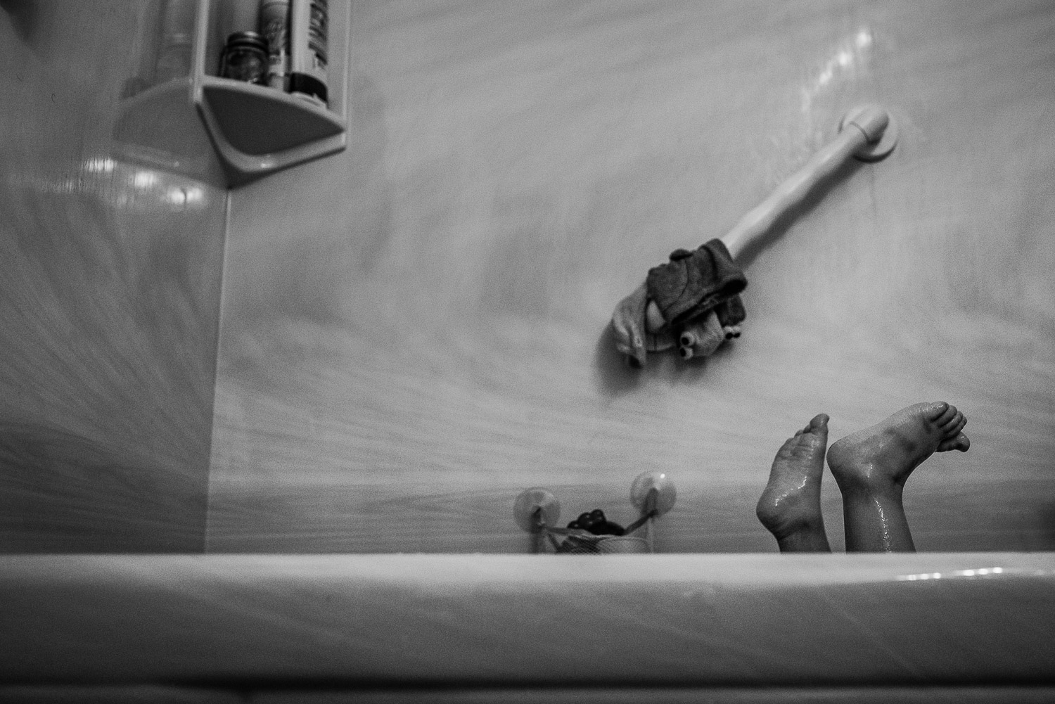 Black and white image of a bathtub with a few toys scattered about and two small toddler feet sticking out without being able to see who they are attached to.