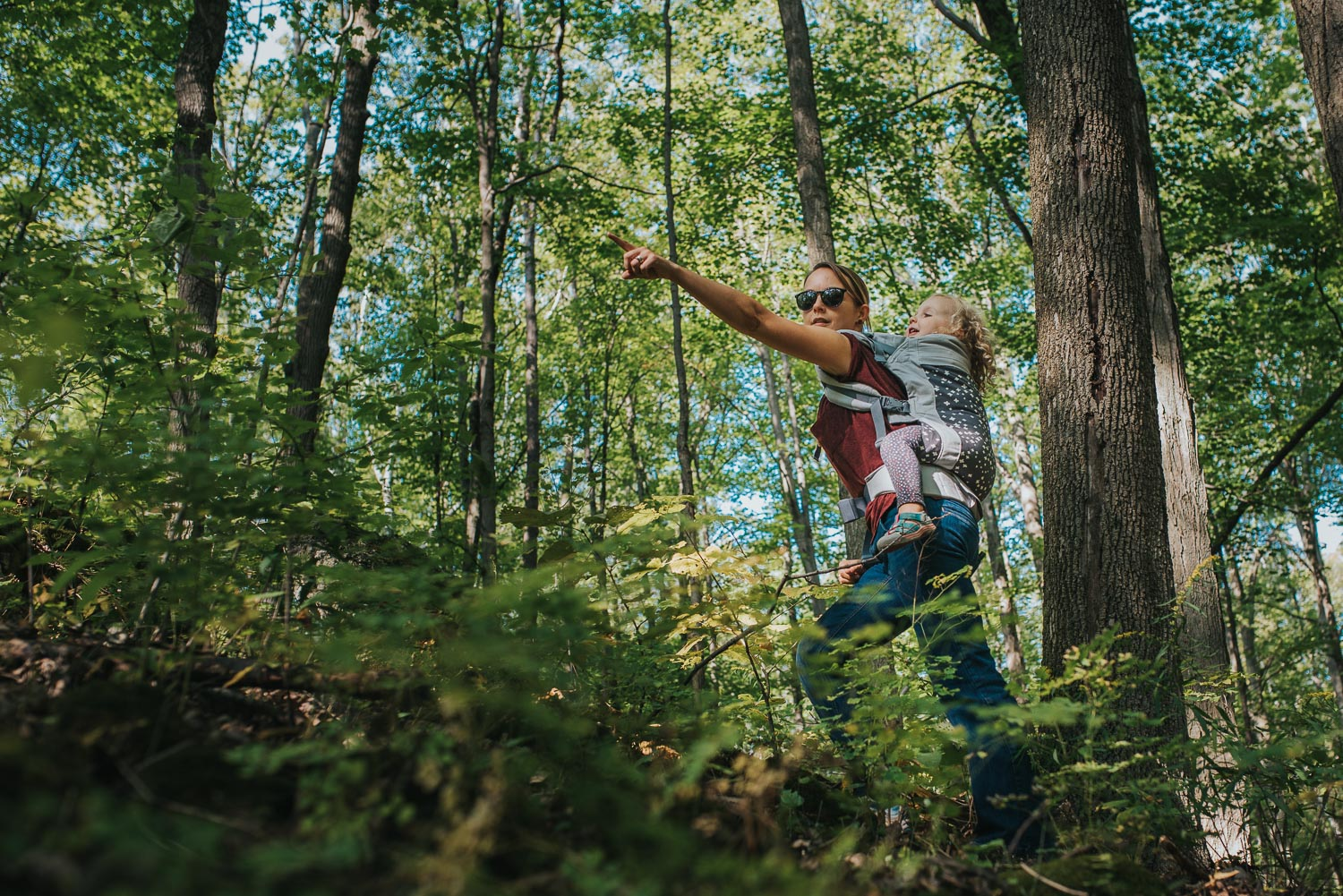 A mother in jeans and a burgundy tshirt with a toddler in a baby carrier on her back hiking up an incline in the woods and pointing off in the distance