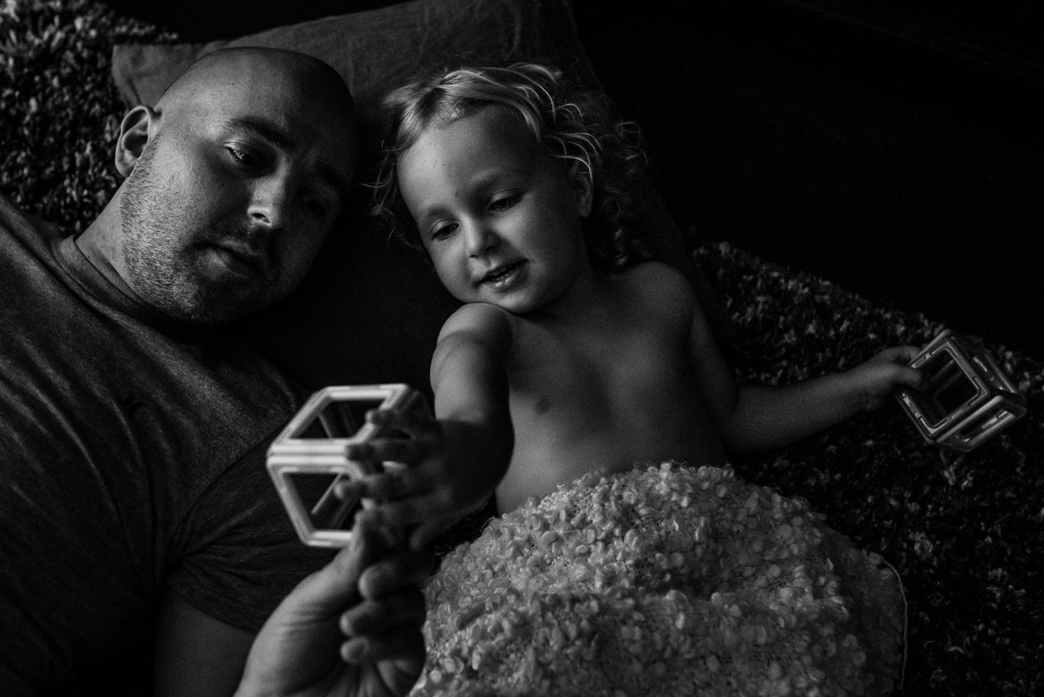 A black and white image of a toddler girl with curly hair and no shirt on laying on a partially carpeted floor with her dad who is bald with a scruffy beard and they are looking at magnet blocks together.