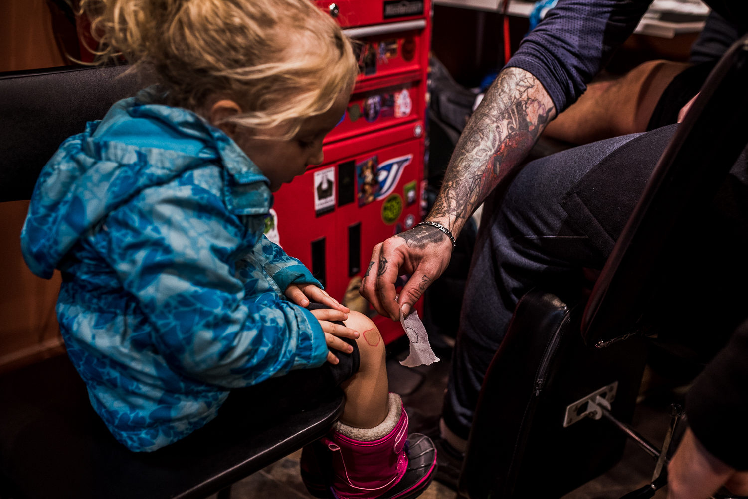 Little girl sitting on a chair in a tattoo parlor