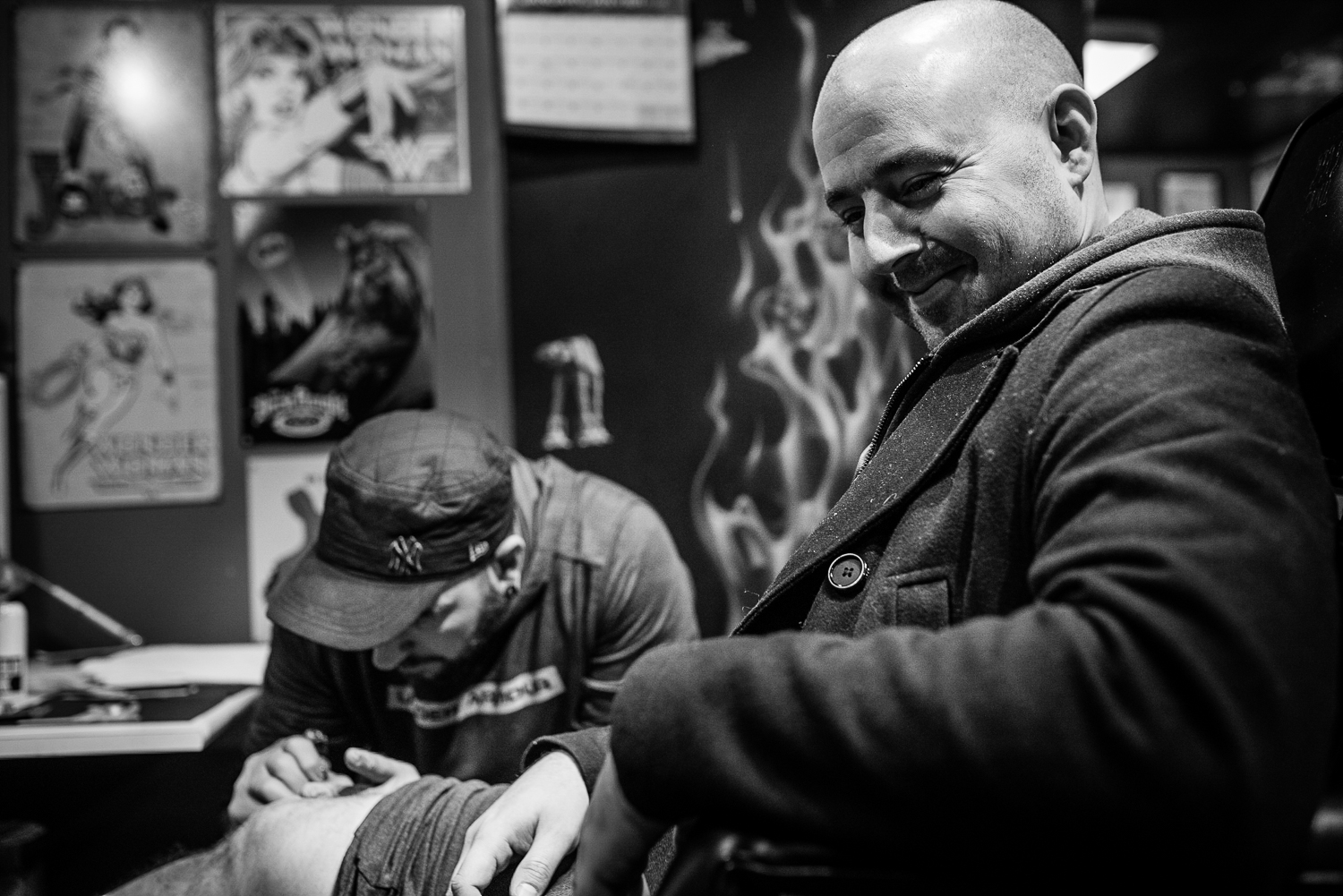 Smiling man getting a tattoo on his knee