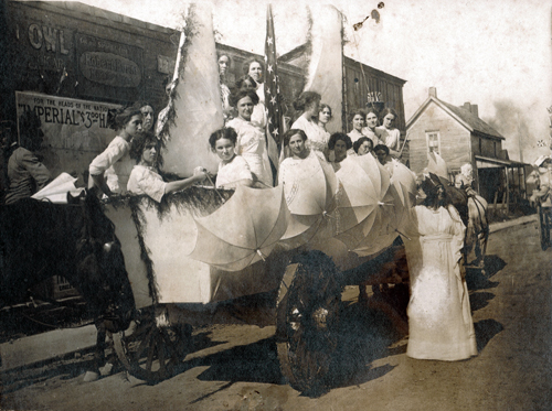 1911 - Ship of State was one of the floats in the first school parade. Lela Bryant, who is dressed as Miss Liberty, is standing on the ground and has a crown on her head. All of the floats were pulled by horses. Courtesy of Archives and Special Collections, Dean B. Ellis Library