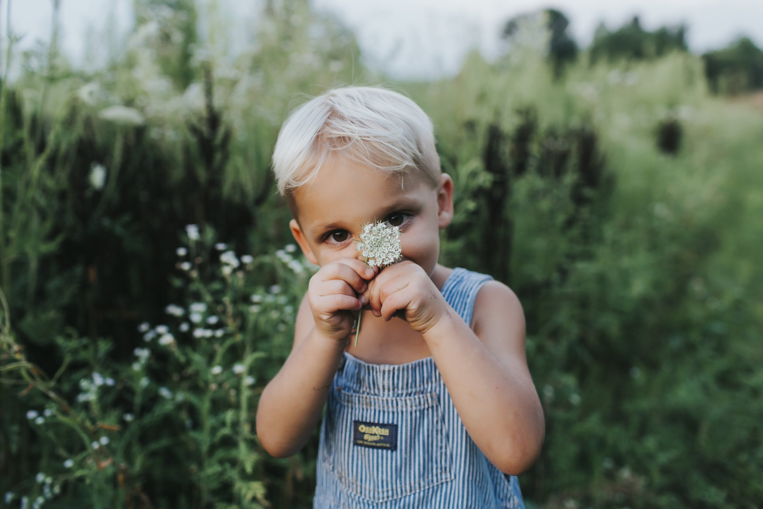 young boy smelling flower