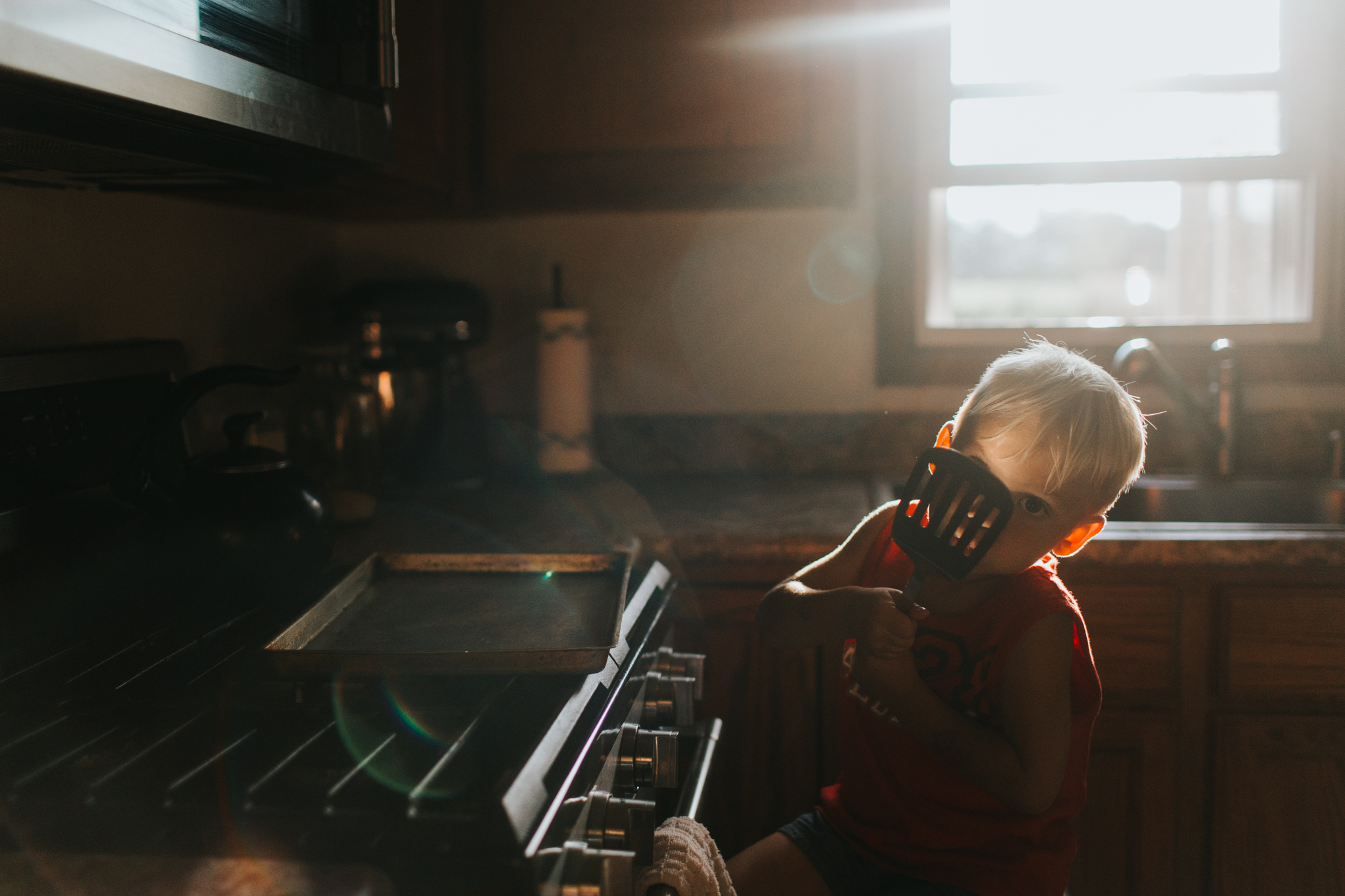 boy baking cookies with spatula in kitchen