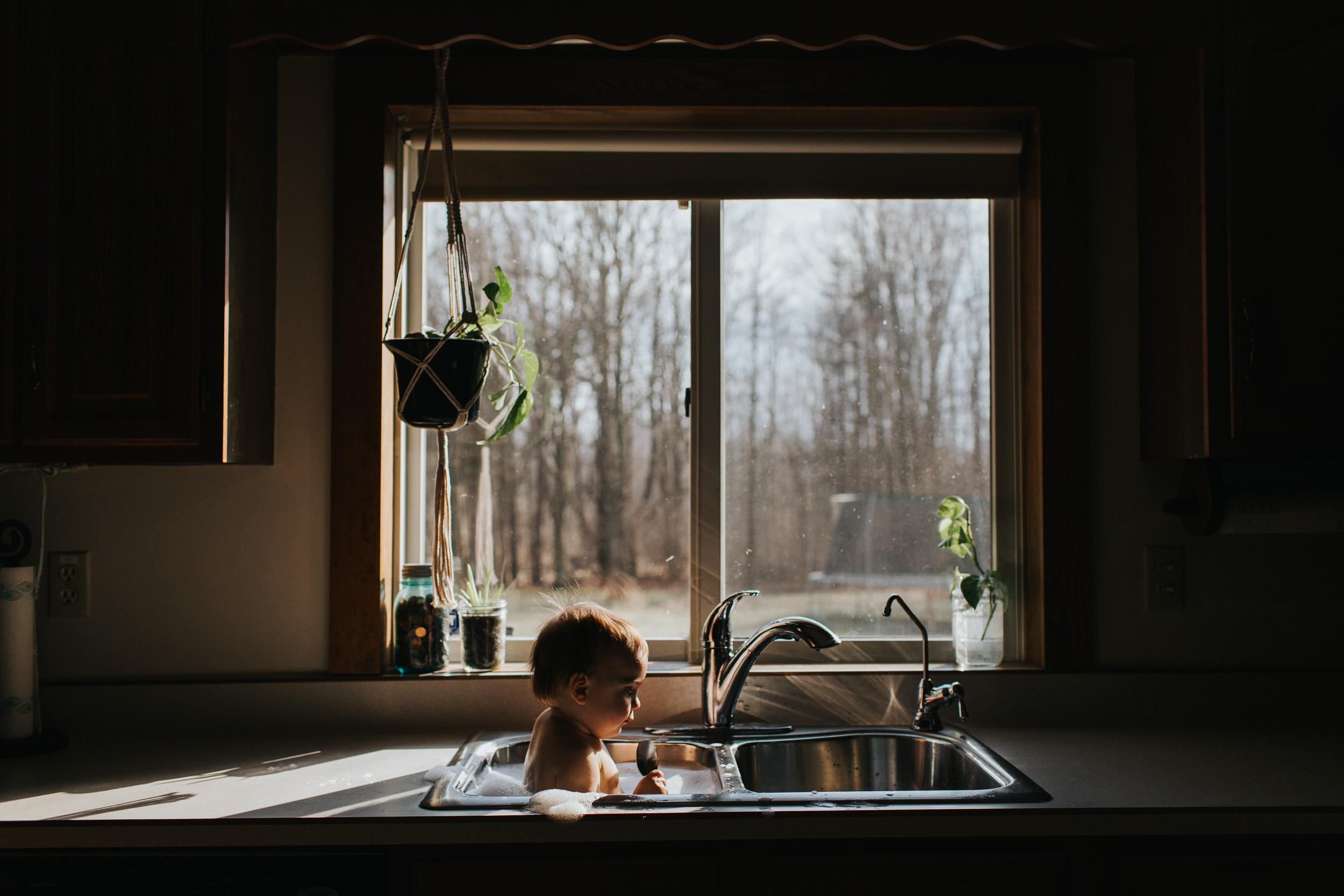 baby in kitchen sink bath