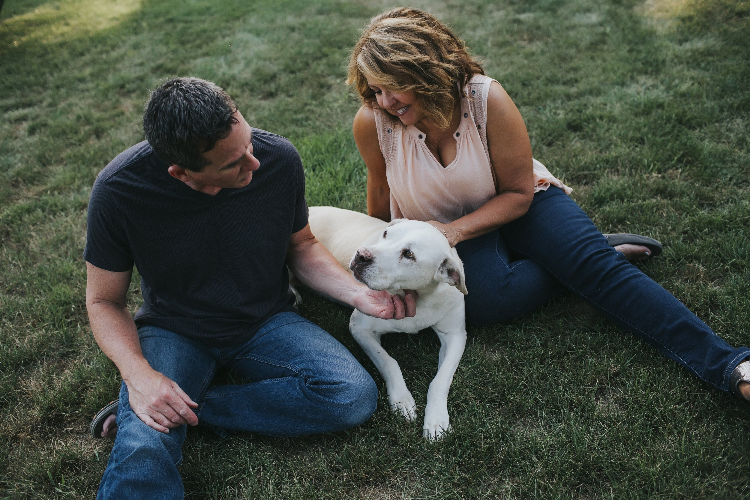 mom and dad with dog on grass