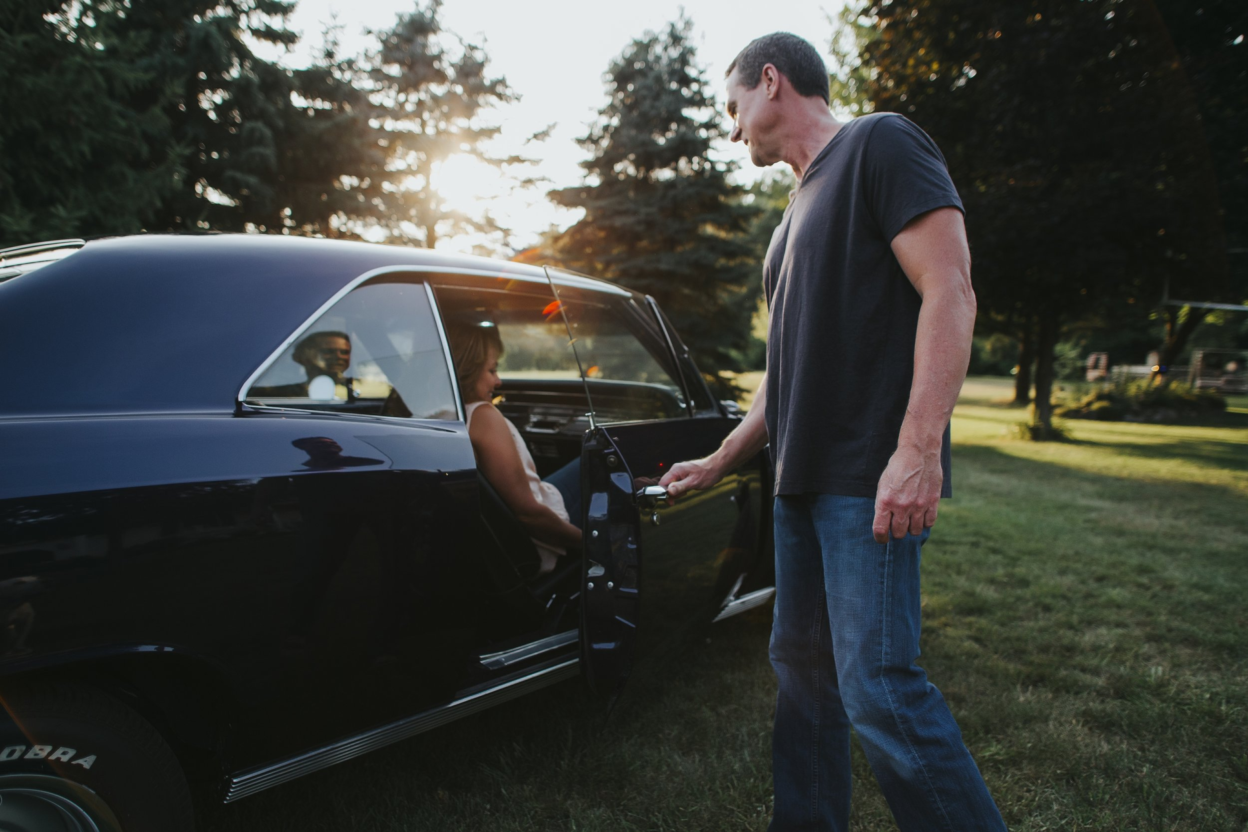 husband holding car door for wife