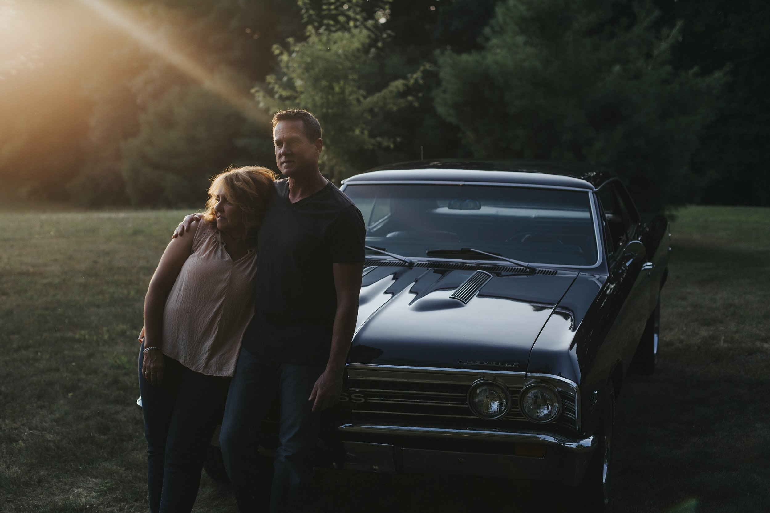 husband and wife leaning against vintage car