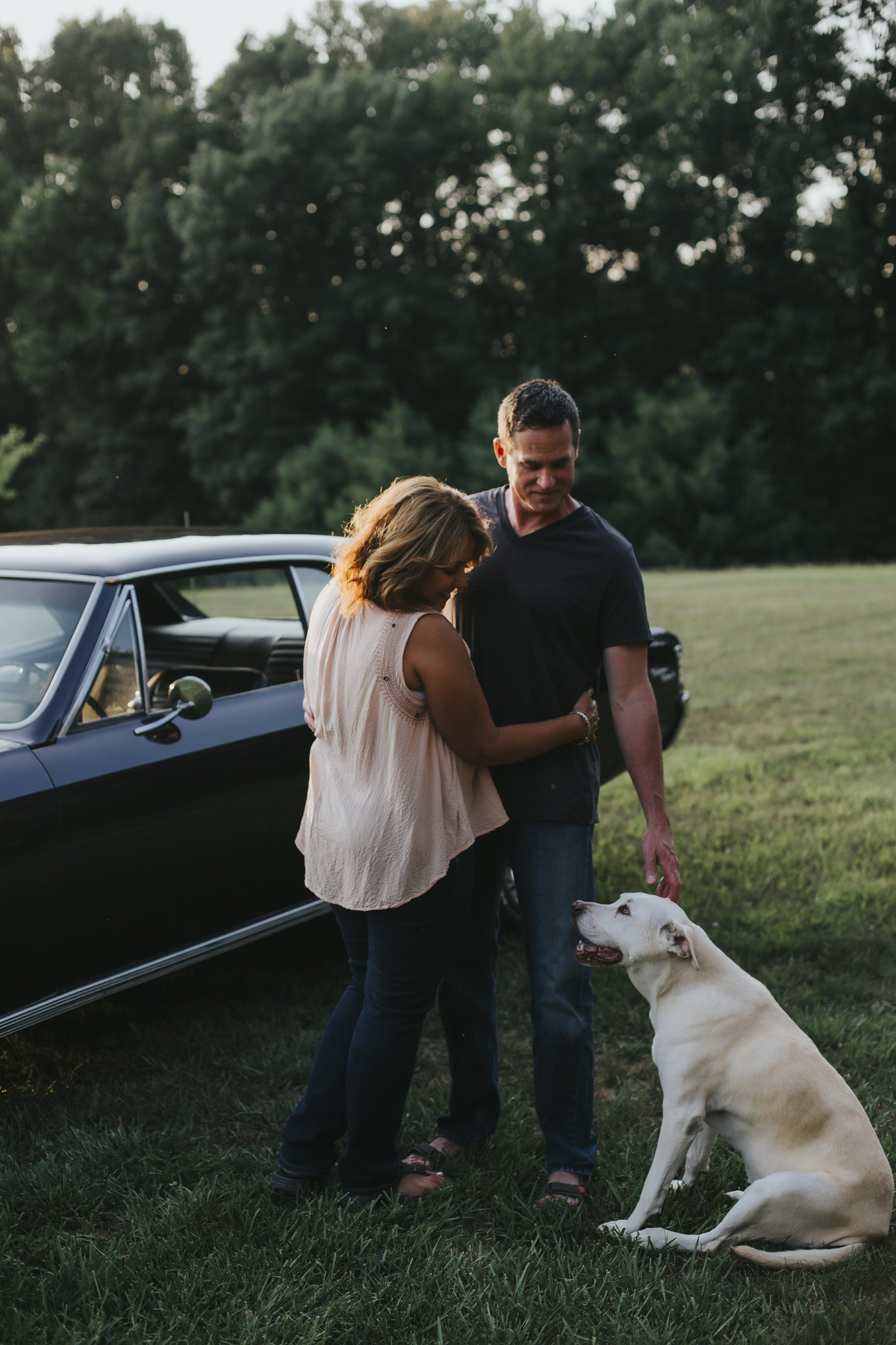couple with dog by old car