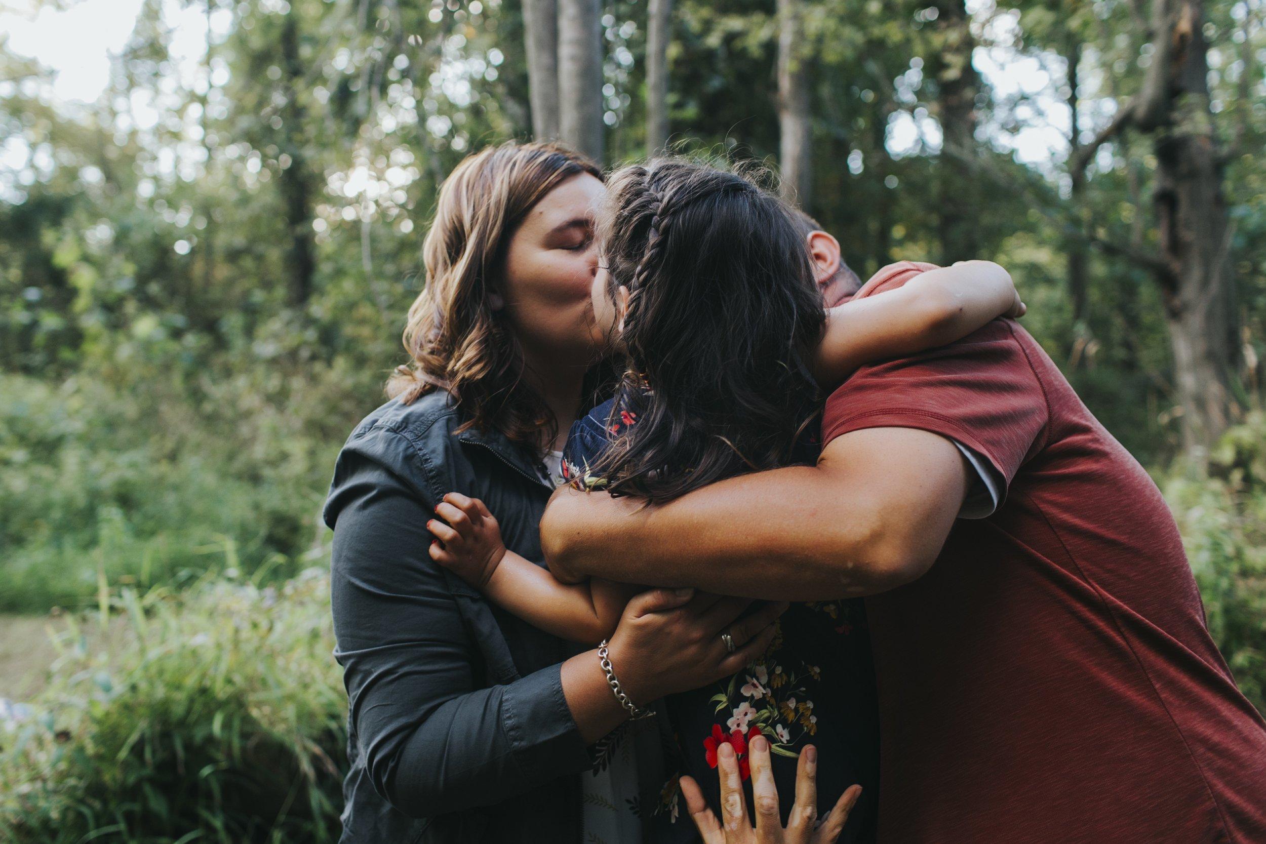 family embracing in creek near kalamazoo, michigan