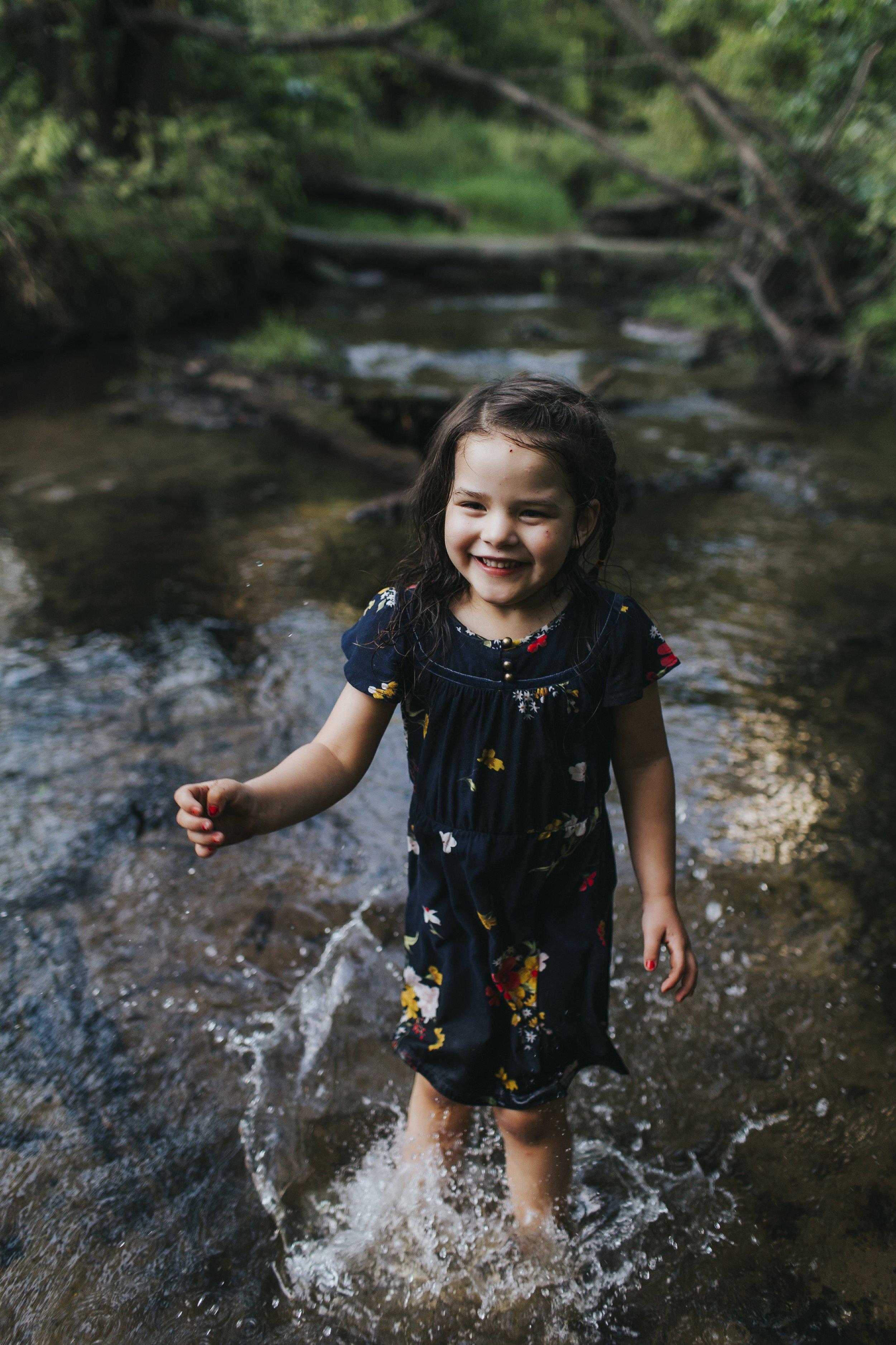 little girl splashing in creek