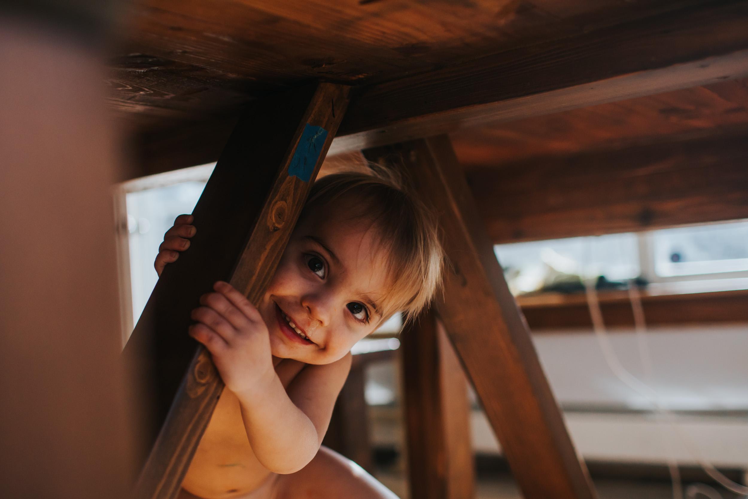 little boy playing peek a boo