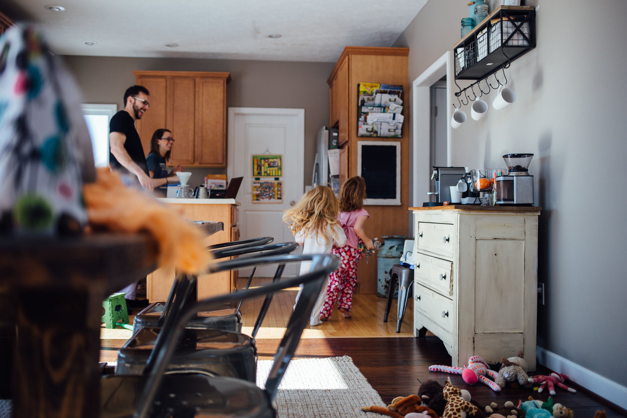 children running through house near galesburg mi while parents watch and laugh
