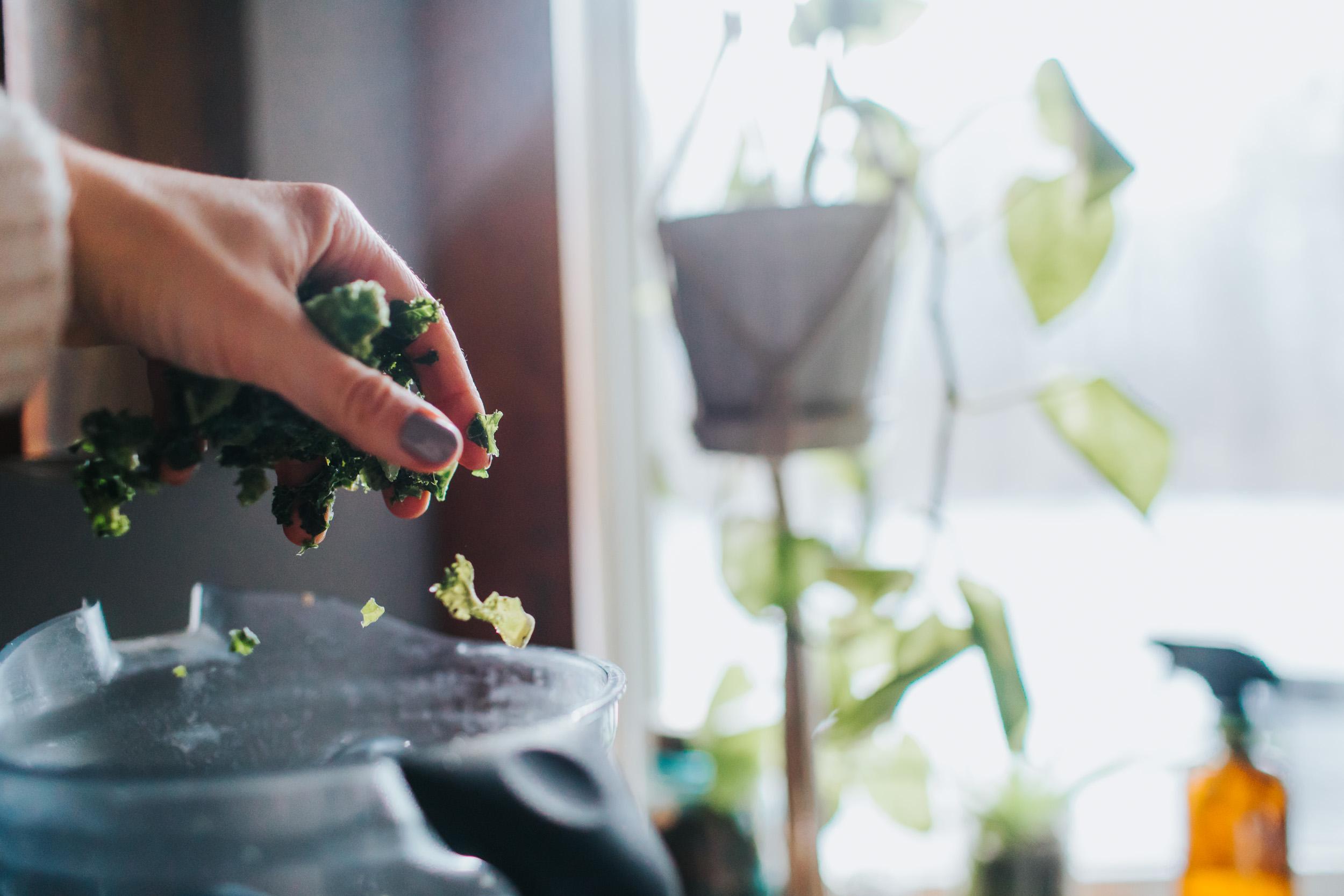 hand sprinkling green kale into vitamix blender
