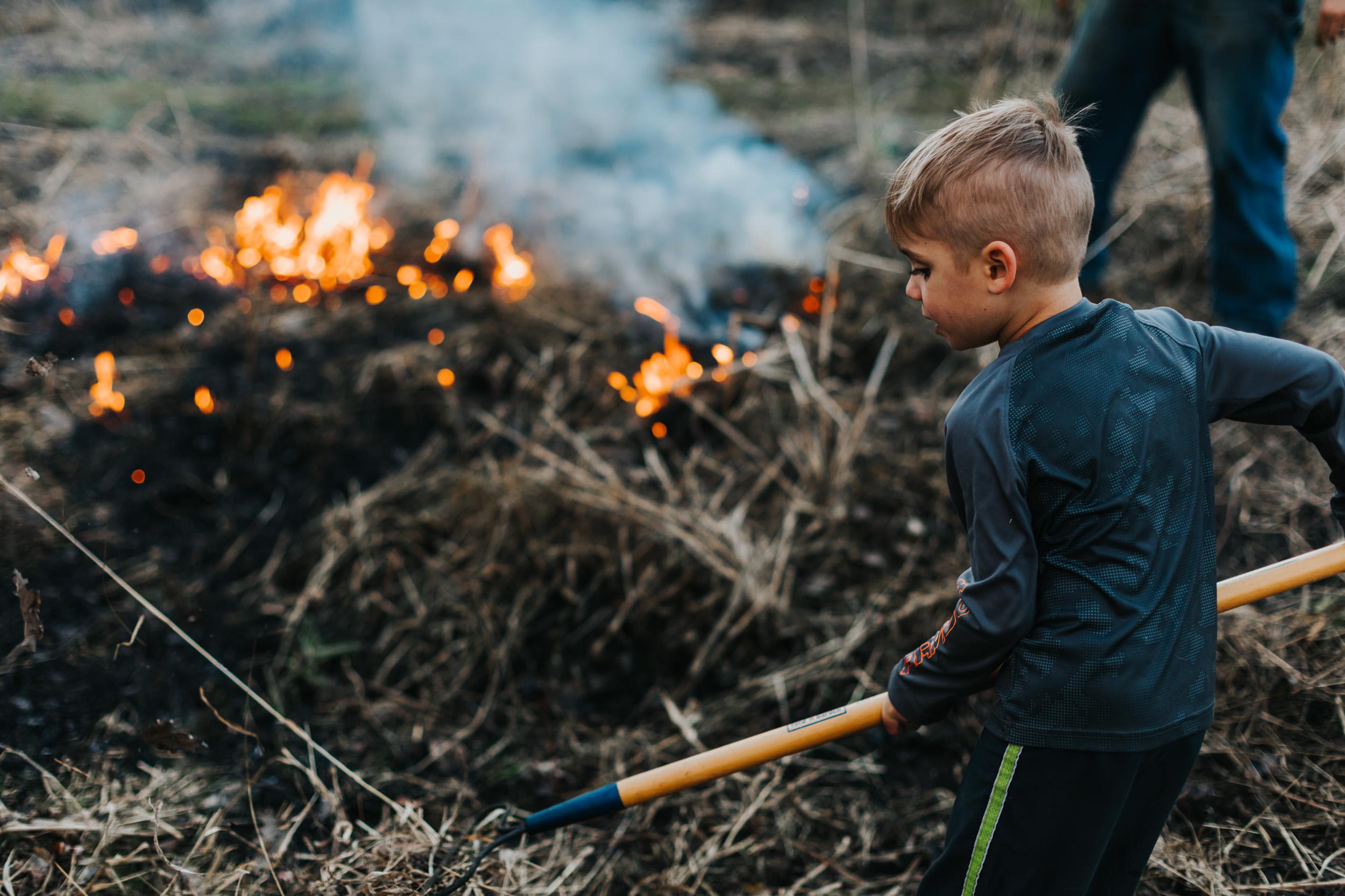 boy raking a fire in a field