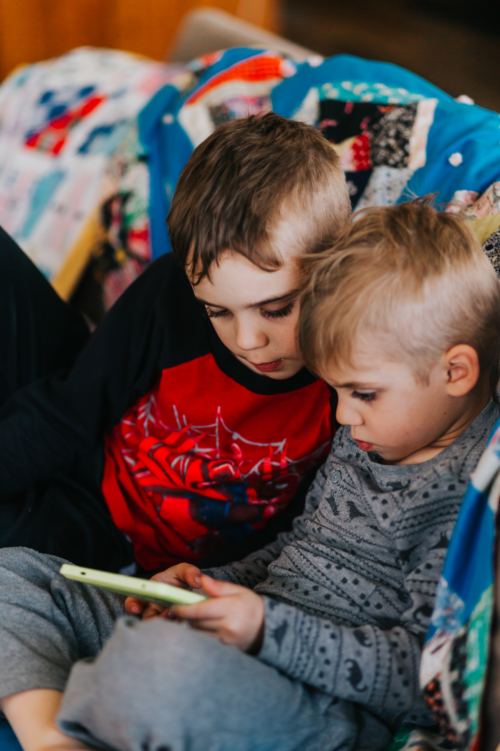 young boys playing on kindle tablet sitting on couch