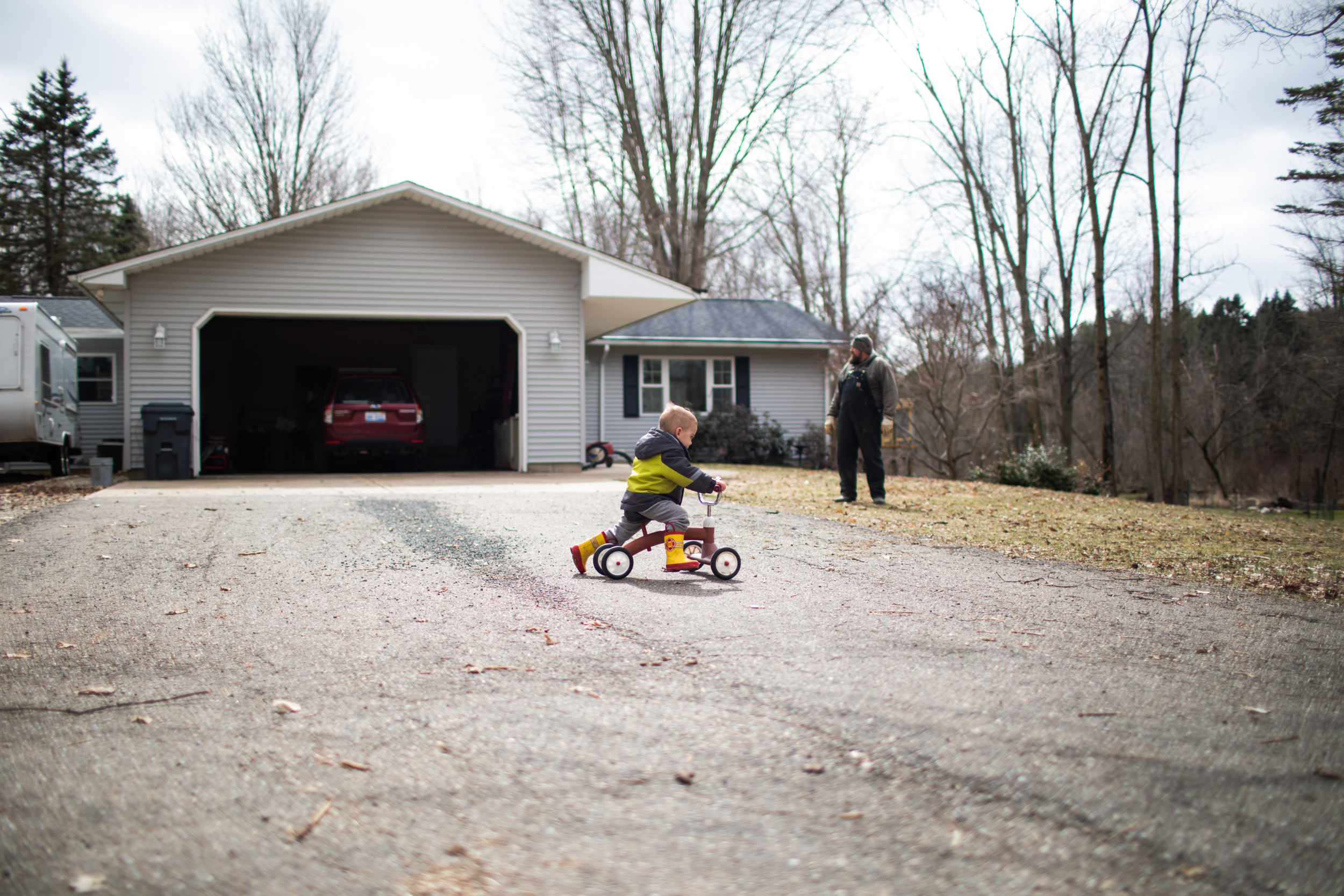 young boy riding tricycle in front of house