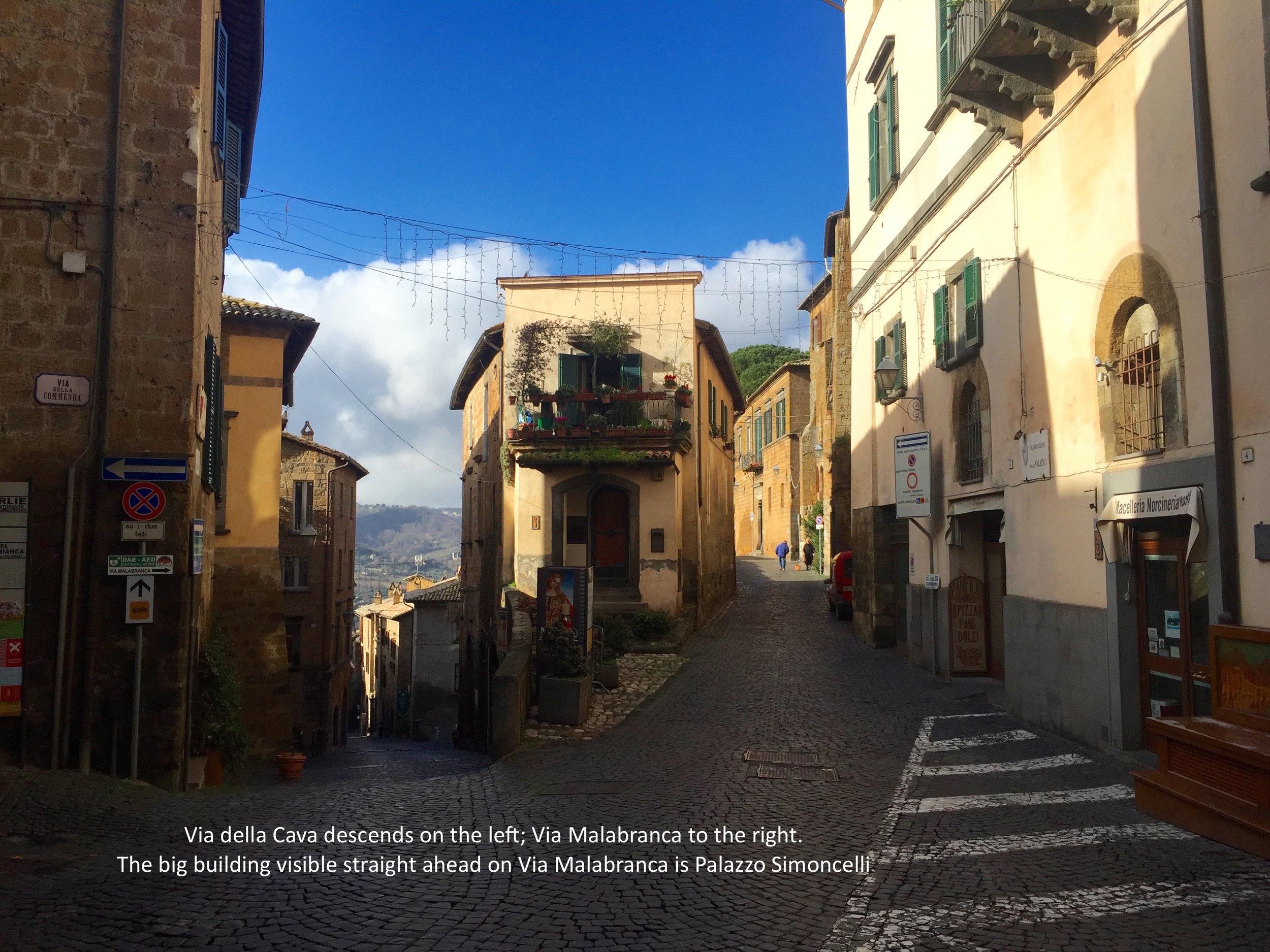 Via della Cava descends on the left to the Porta Maggiore. Via Malabranca is the right fork of the Y. Palazzo Simoncelli is the sun-lit building straight ahead on Via Malabranca.