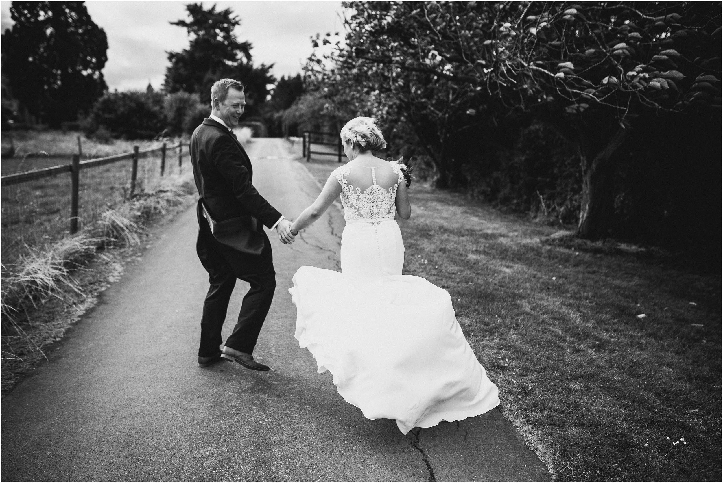 Brides dress gets blown by the wind at Overstone park Northamptonshire
