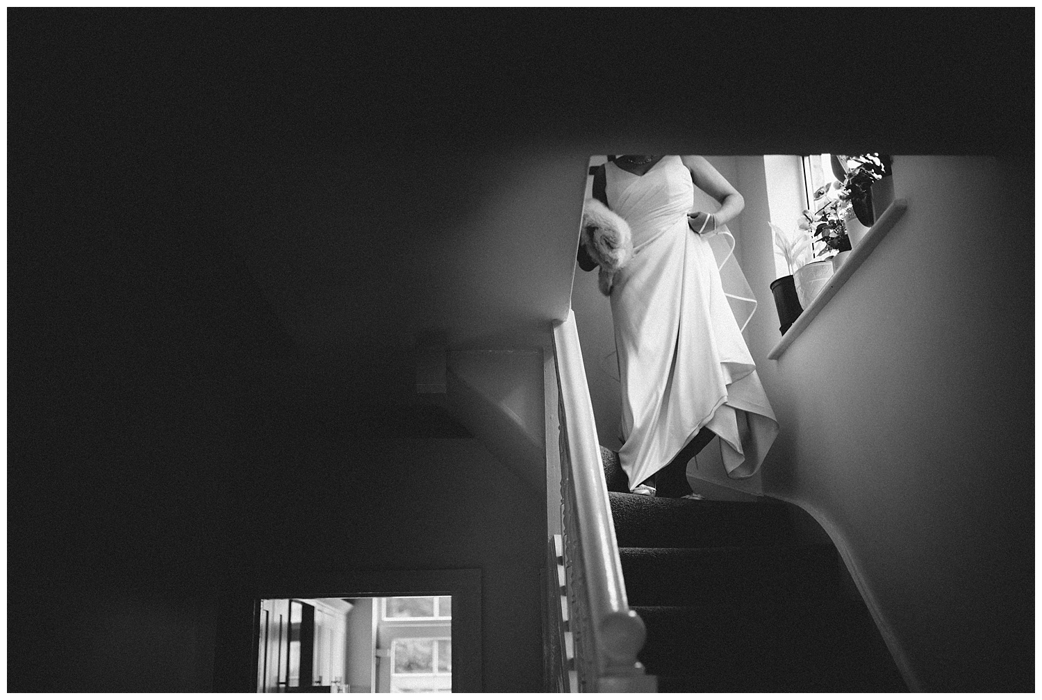 Bride coming down stairs during bridal preparation with her wedding dress on