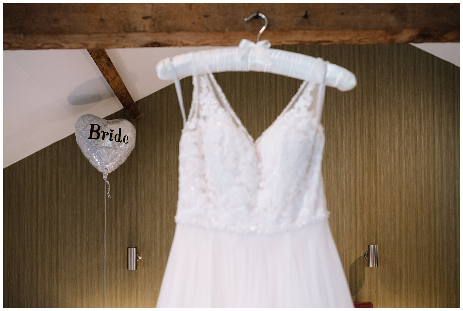 Brides wedding dress hanging on beam with bride balloon in background during bridal prep at the Granary Fawsley