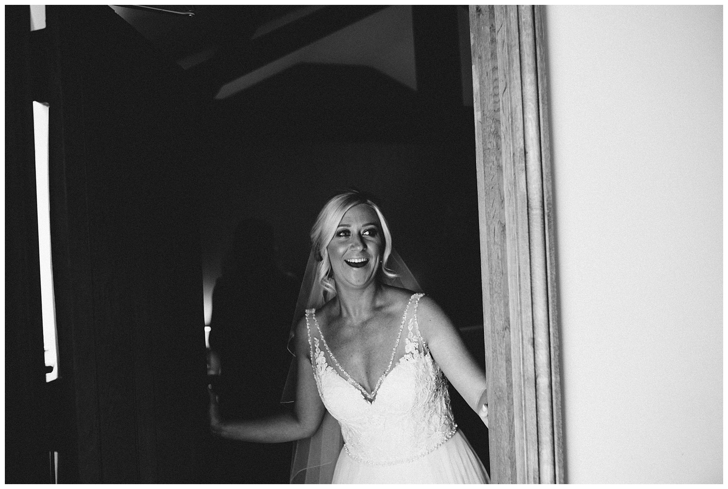 Bride opens door to reveal her wedding dress dress during bridal prep at the granary at fawsley