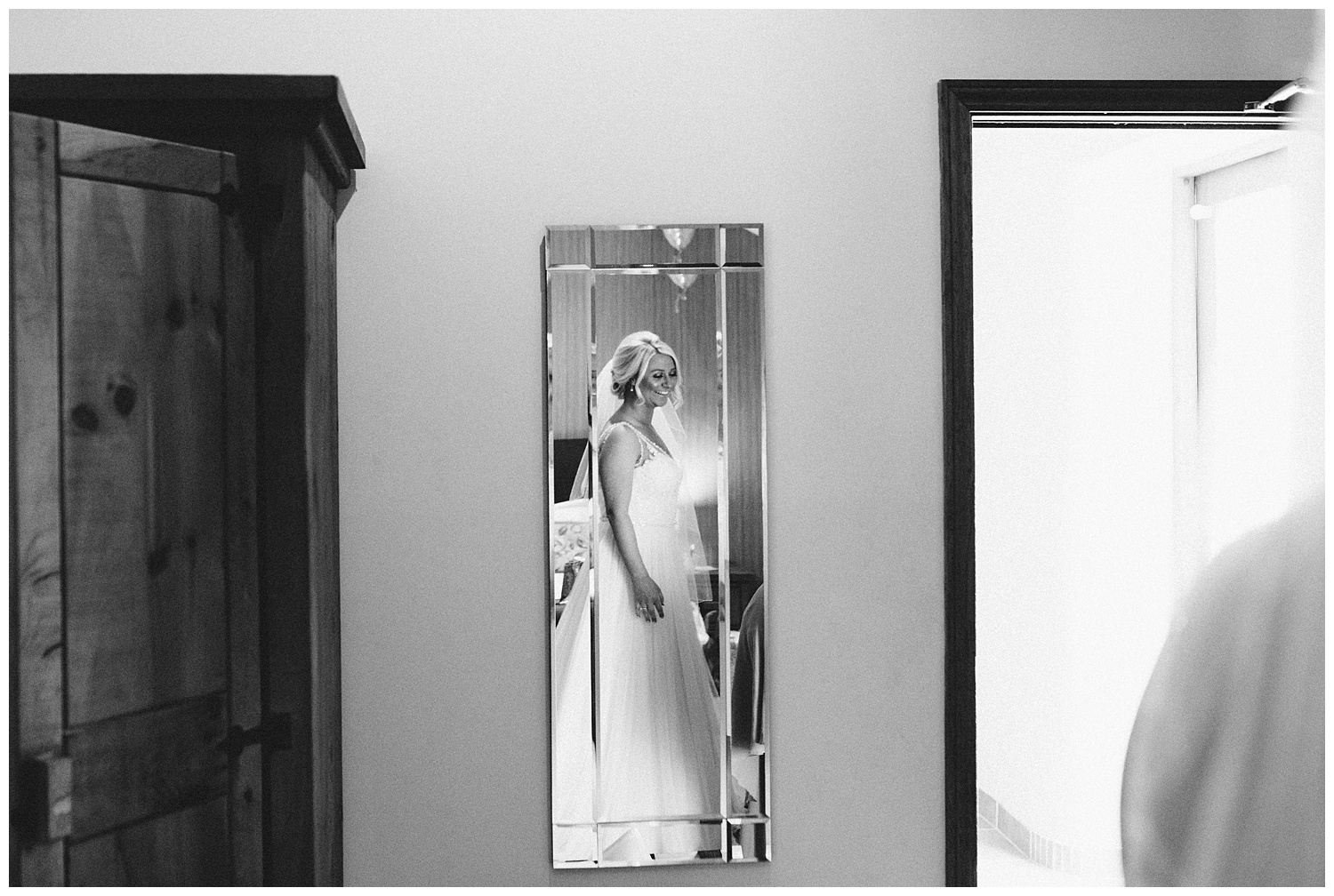 reflection of bride in mirror during bridal prep at the granary in fawsley