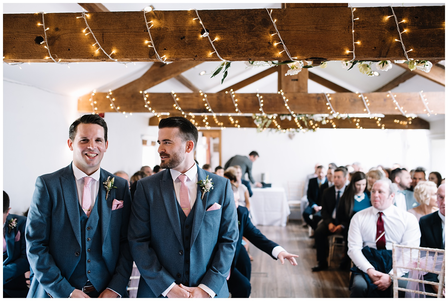 groom nervously waiting for bride to walk up the aisle and talking to his best man during wedding ceremony at the granary at fawsley