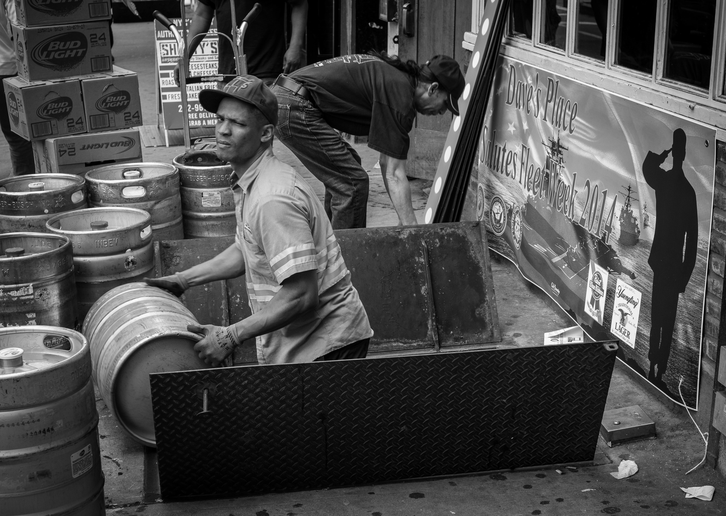 In street photography,you have to always be ready to shoot. In this case I noticed the Fleet Week sign and the man loading kegs as I walked by. I quickly turned and got off about a dozen frames before I moved on. 1/125, f5.6 at ISO 500.