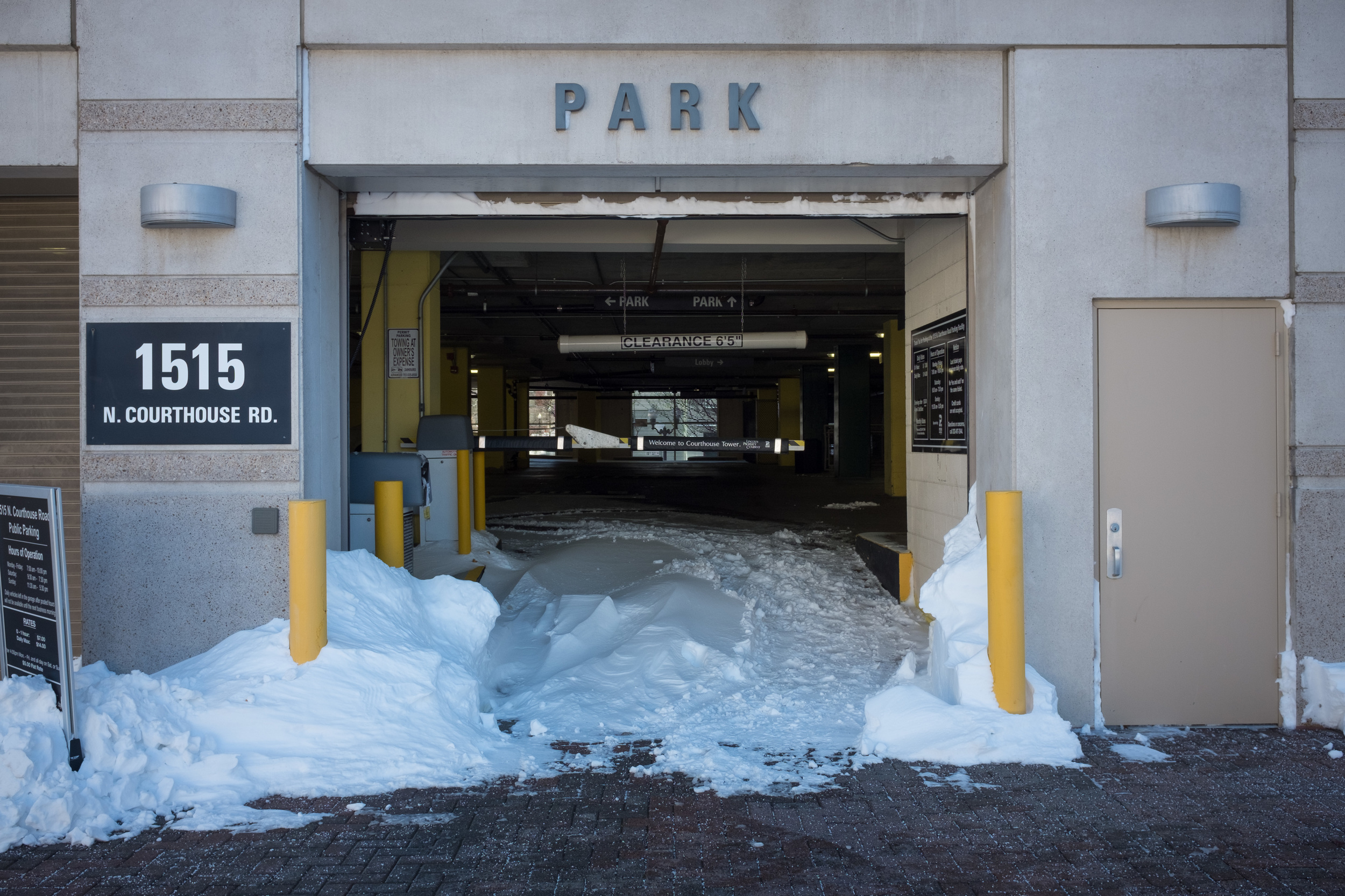 What drew my eye to this scene was just how far-reaching and intrusive the snow was, even entering the parking garage that no cars had entered. I also like the symmetry of the opening and the splash of color from the poles.