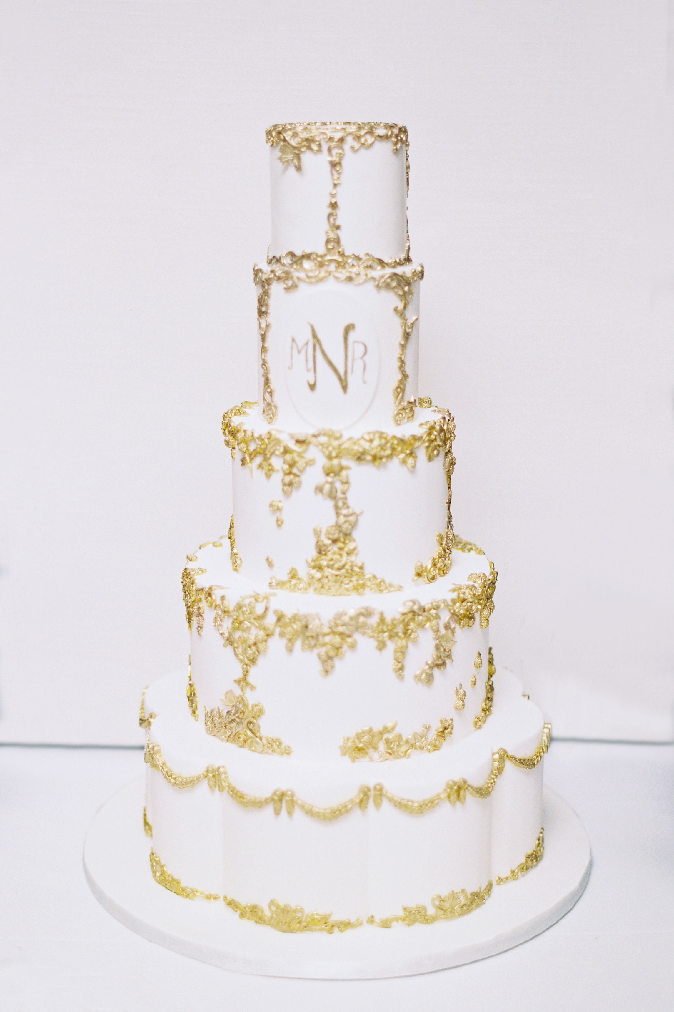 White wedding cake with gold bas relief and monogram