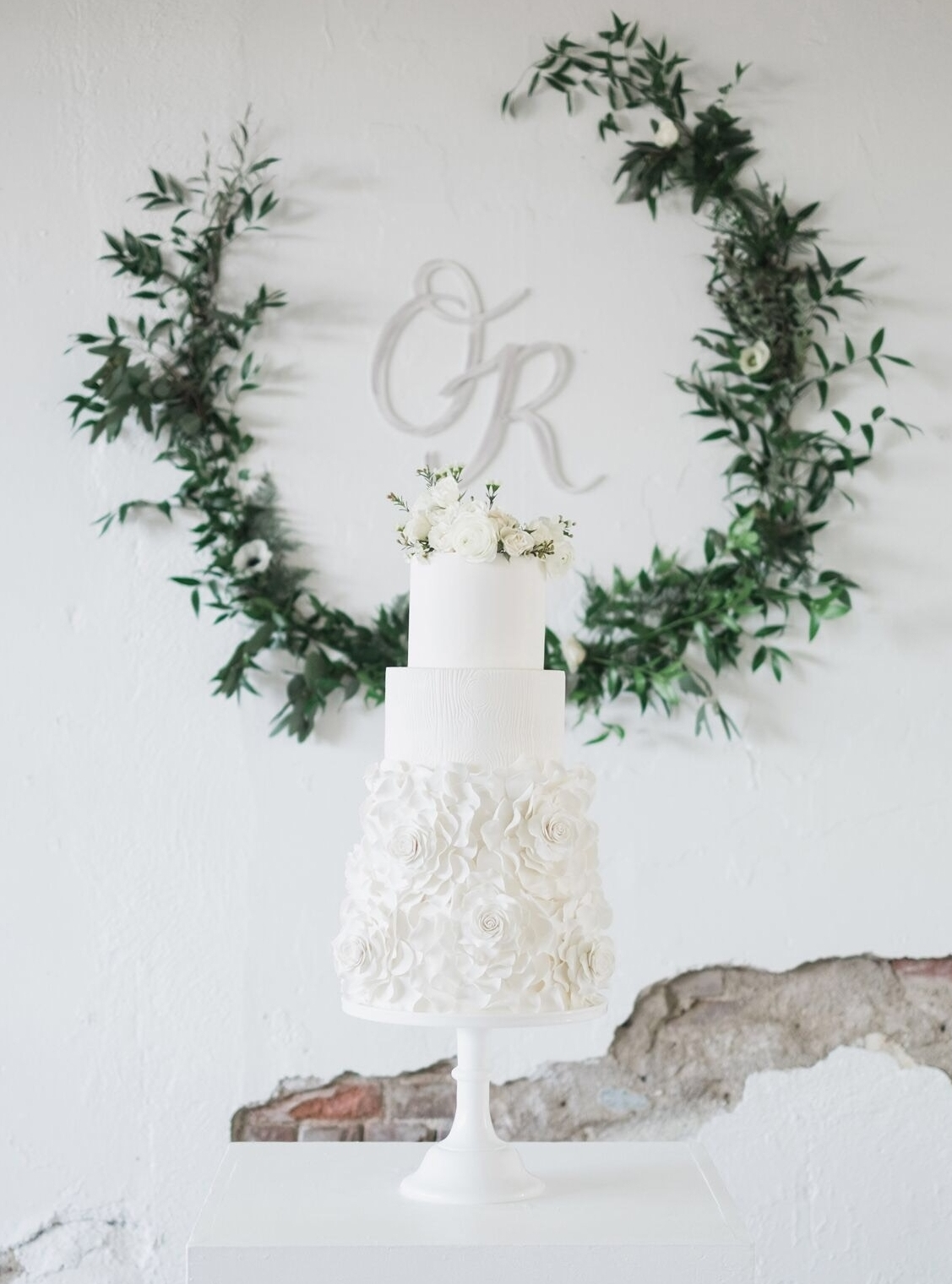 White wedding cake with cascading sugar flowers and wood grain