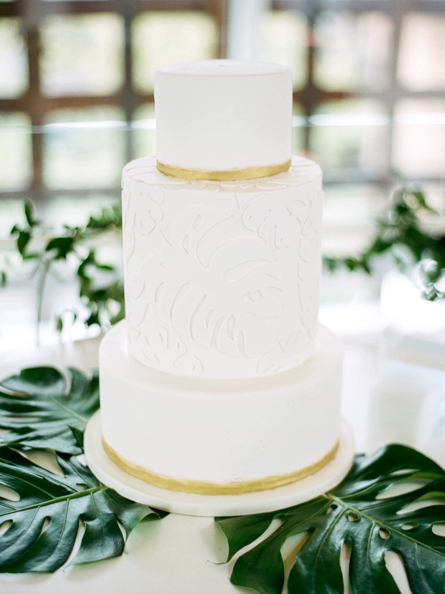 White and gold tropical wedding cake