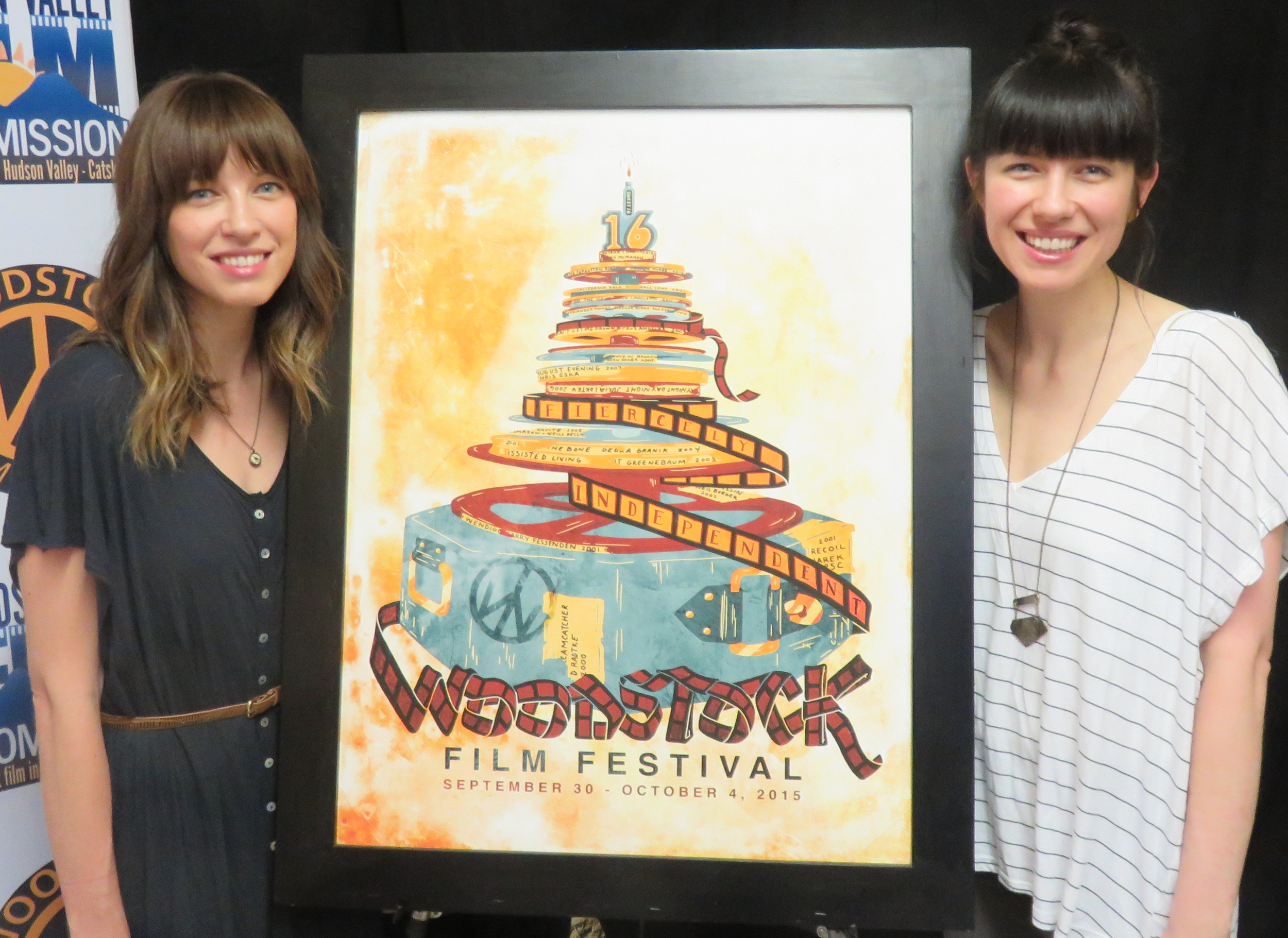 Joy + Noelle showing off the 2015 Woodstock Film Festival poster, designed by them