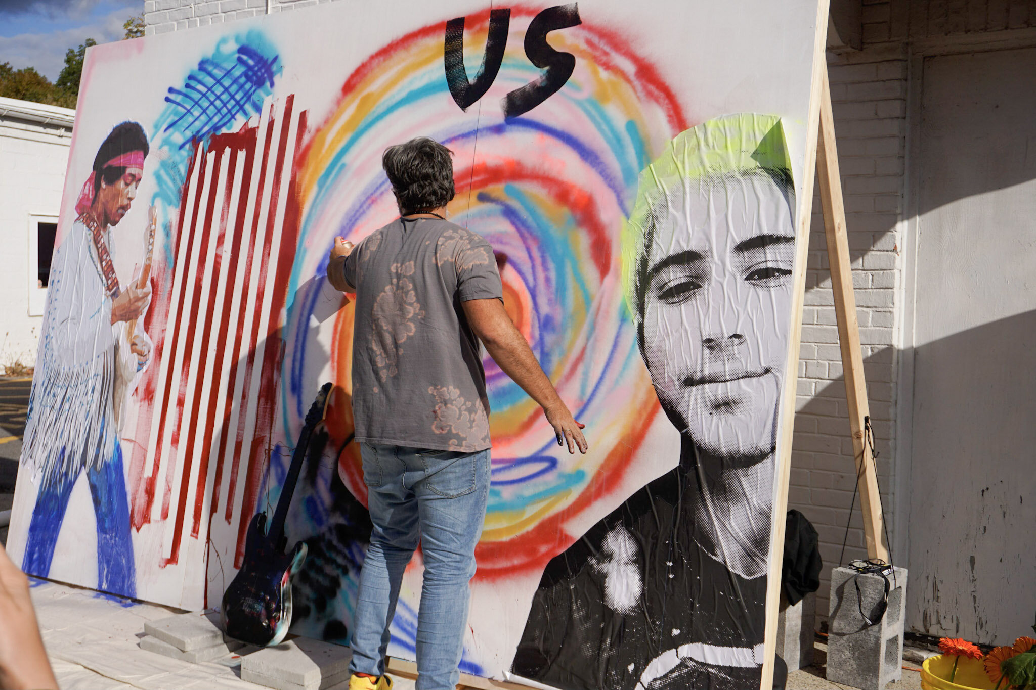 Manuel Oliver works on his mural in the center of Woodstock.