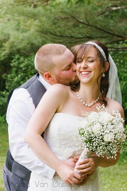 groom_kissing_brides_cheek_bouquet.jpg
