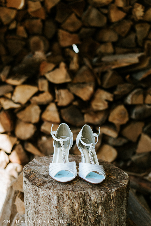 davids_bridal_shoes_firewood_rustic_wood_pile_wedding_chic_bridal_footwear_connecticut_wedding_photographer.jpg