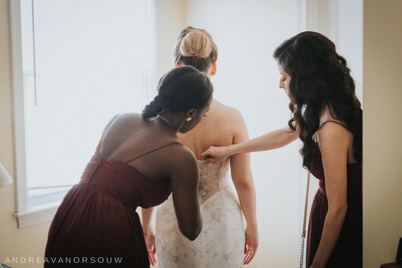 wedding_dress_bridesmaids_buttoning_button_elaborate_Window_light_red_dresses_connecticut_wedding_photographer.jpg