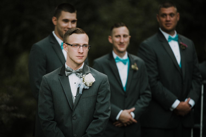 groom_reaction_bride_aisle_tears_joy_blue_suit_white_boutonnaire_adventure_outdoors_trees_dress_outdoors_connecticut_rhode_island_massachusetts_new_england_wedding_photography_photographer_natural_laid_back_fun_light_engagement_session.jpg