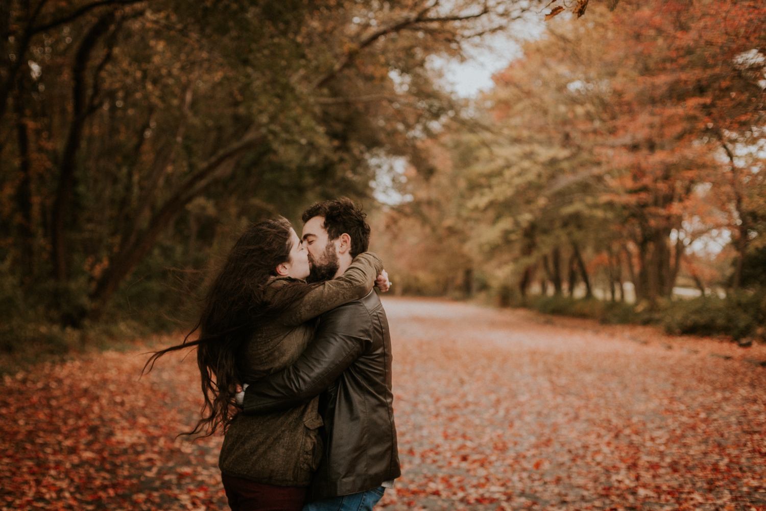 fall_colt_state_park_leaves_foliage_engagement_kiss_motion_wind_orange_leather_parka_outdoors_trees_dress_outdoors_connecticut_rhode_island_massachusetts_new_england_wedding_photography_photographer_natural_laid_back_fun_adventure_light_engagement_session.jpg