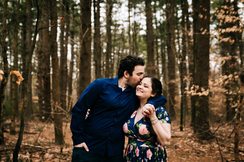 Man kissing floral dress wearing woman in woods near Santa Fe